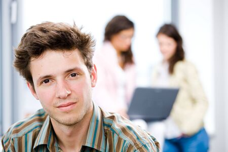 Young happy businessman looking at camera, smiling while business team working in background. Stock Photo - 4107032