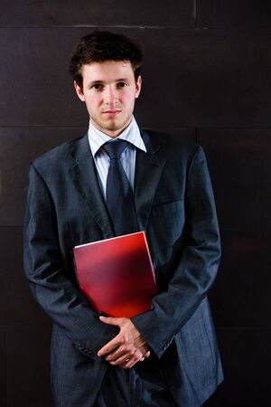 Portrait of satisfied young businessman in grey suit standing at office corridor. photo