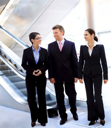 Happy young businesspeople walking and talking in office lobby. photo