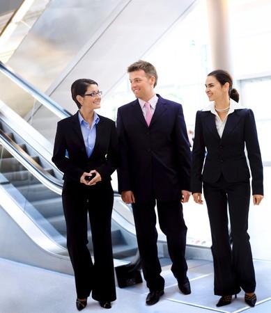 together with long tie: J�venes empresarios feliz caminar y hablar en el vest�bulo de la oficina. Foto de archivo