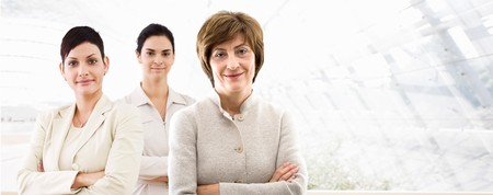Happy team of three businesswomen standing in front of windows inside officebuilding, smiling. Business banner.  Stock Photo