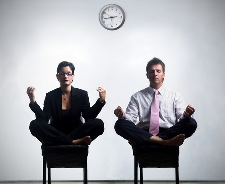 Young business people in an abstract office enviroment are sitting in yoga lotus-pose and relaxing. Stock Photo