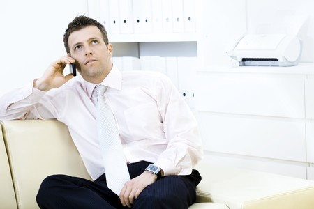 Mature businessman sitting on sofa and calling on mobile phone at office. photo