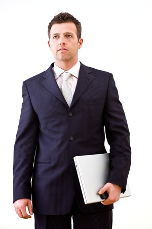 Determined successful businessman standing and holding laptop computer in hand. Isolated on white background. photo