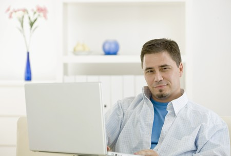 Happy casual man teleworking using laptop computer at home. photo