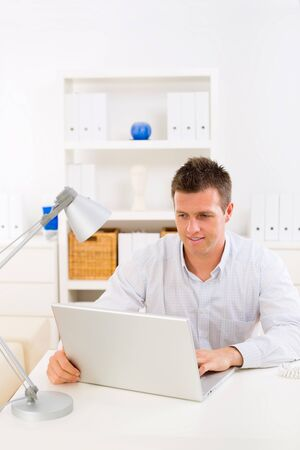 Business man working on laptop computer at home. Stock Photo - 4121276