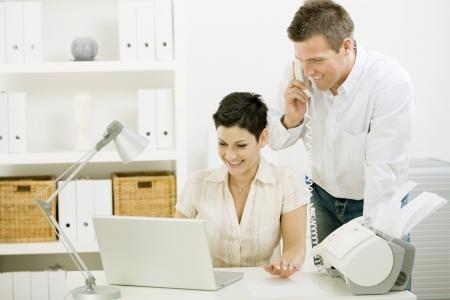 outwork: Feliz pareja de trabajo en casa usando ordenador port�til, sonriendo.
