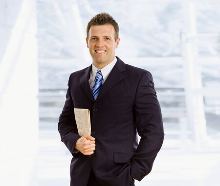 Happy businessman holding newspaper indoor smiling photo