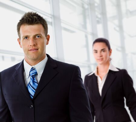 Businessman and businesswoman standing at office lobby. photo