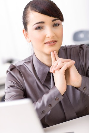 Young businesswoman thinking in her office, interlocking his hands. Stock Photo - 4121284