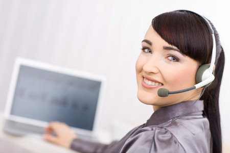 Young female operator wearing a headset works on her laptop, looking at camera. Stock Photo - 4121279