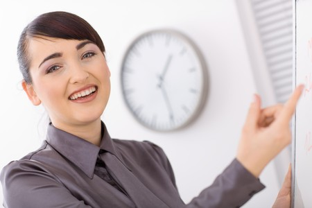 Happy businesswomen doing presentation on whiteboard, smiling. Stock Photo - 4121280