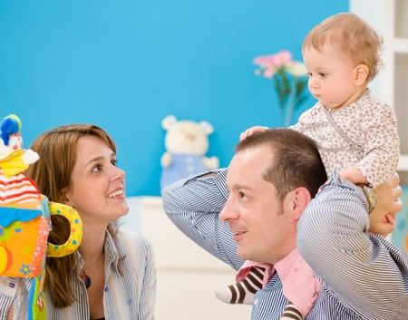 Happy family playing together: mother, father and 1 year old baby girl at children's room, smiling. Toys are officially property released. Stock Photo - 4121356