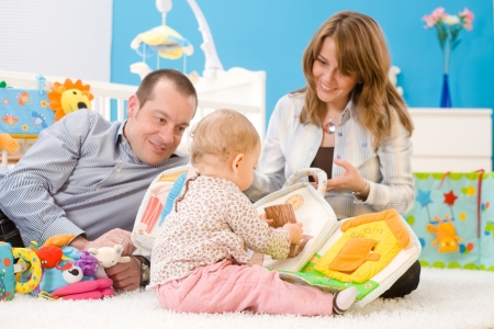 Happy family playing together: mother, father and 1 year old baby girl sitting on floor at childrens room, smiling. Toys are officially property released. photo