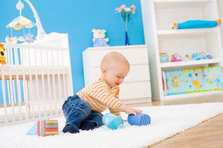 1 year old: Happy baby boy (1 year old) sitting on floor at childrens room and playing with toy blocks. Toys are officially property released. Stock Photo