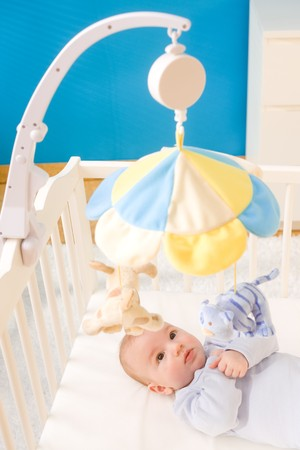 Little baby boy playing with hanging toy on crib. Toys are officially property released. photo