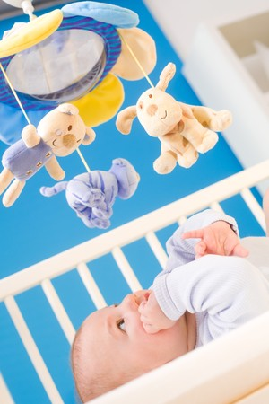 hanging toy: Infant paying attention to hanging toy in baby bed. Toys are officially property released. Stock Photo