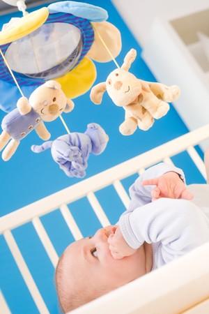 Infantil prestando atención a la horca bebé de juguete en la cama. Los juguetes son propiedad oficialmente puestos en libertad. Foto de archivo - 4121335