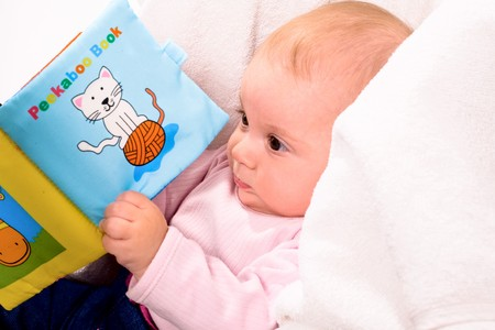 Baby playing with story book sitting in baby carrier. Stock Photo - 4121319