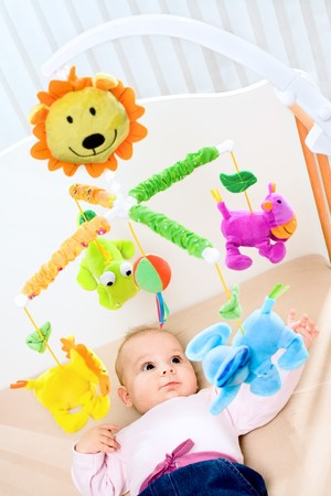 Happy baby playing with bed side toy, smiling. Stock Photo - 4121316