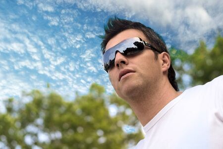 Young man wears futuristic sunglasses and looks at the future. photo