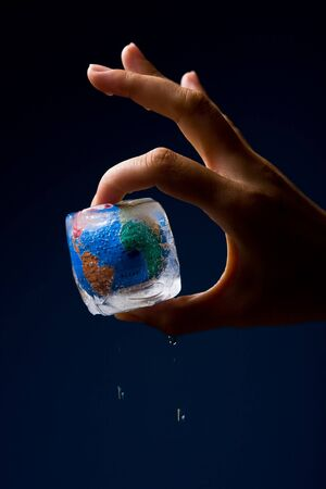 thawing: Conceptual image of global warming and green environmentalism. Human hand holding earth globe frozen into thawing ice cube.