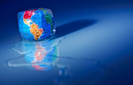 environmentalism: Conceptual image of global warming and green environmentalism. Earth globe frozen into thawing ice cube.