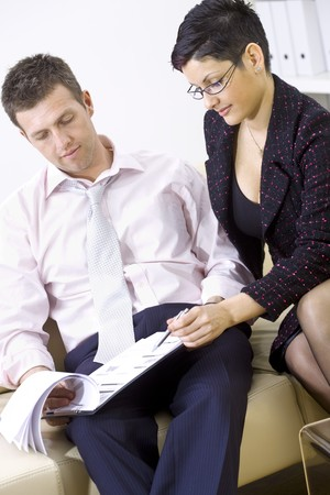 stitting: Businesspeople working together, stitting on couch looking at business documents. Stock Photo