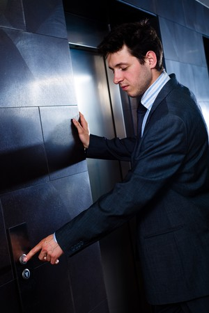 businessman waiting call: Young hapy businessman standing at office in front of elevator. Stock Photo