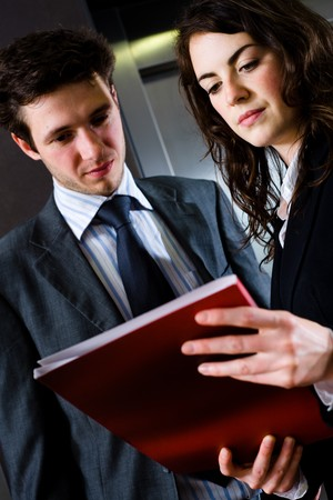 Young businesspeople working together at office corridor, looking at red document folder, reading reports. photo