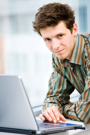 Casual looking happy businessman working on laptop computer in front of office window, smiling. photo