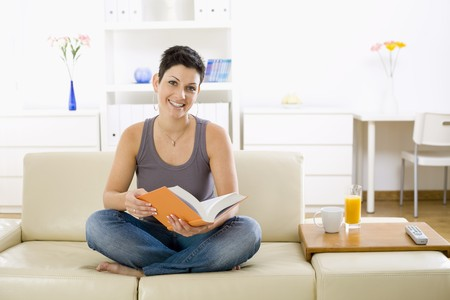 Female student sitting on sofa at home, reading book. photo