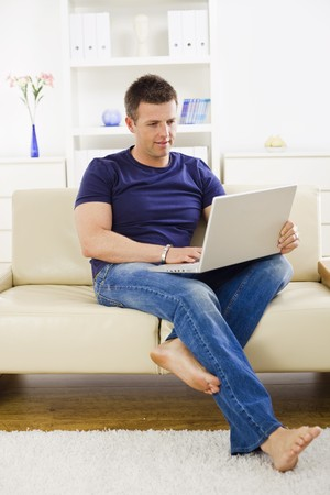 Man browsing internet on laptop computer at home. photo