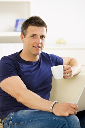 Man sitting on sofa at home and using laptop computer. Stock Photo - 4130485