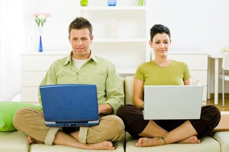 outwork: Pareja feliz trabajando en ordenador port�til en casa, sonriendo.
