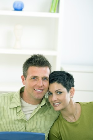 outworking: Happy love couple cuddling at home, smiling.