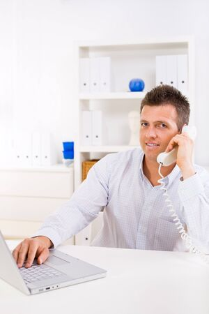Business man working on computer at home calling on phone. Stock Photo - 4130461