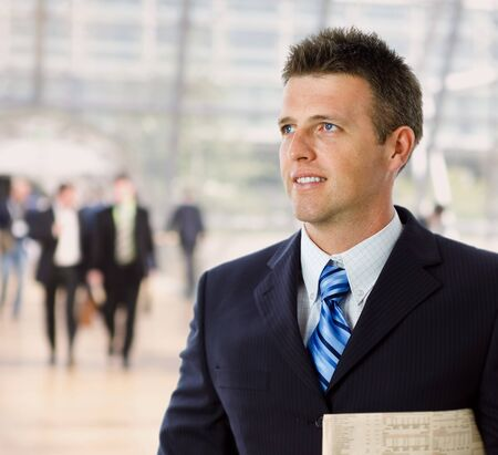 Portrait of happy successful businessman holding newspaper, smiling. photo