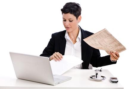 businesswear: Businesswoman reading financial newspaper, white background.