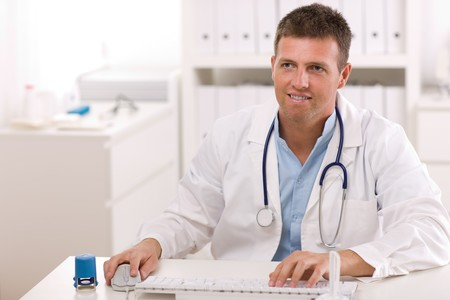 Happy male doctor working at office, smiling. Stock Photo - 4130446