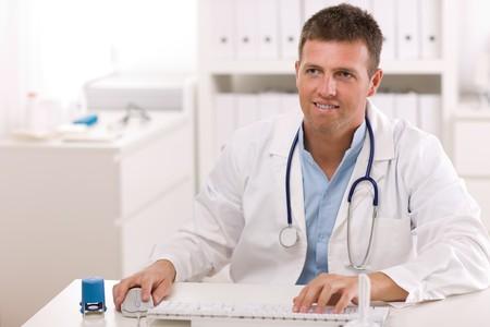 male doctor: Happy medico di sesso maschile che lavorano in ufficio, sorridendo.