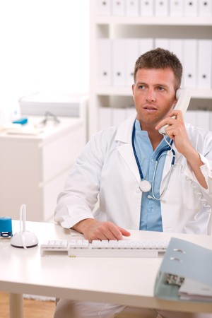 Medical doctor talking on phone at office. Stock Photo - 4130443