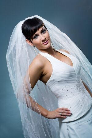Bride posing and smiling wearing classic white wedding dress and veil. photo