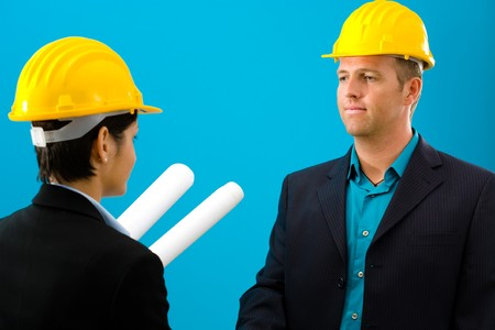 Arhitects shaking hands isolated on blue background. photo