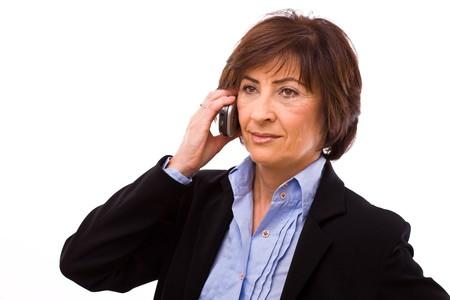 mobilephones: Senior businesswoman calling on mobile phone isolated on white background. Stock Photo