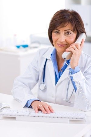 Senior female doctor calling on phone, smiling. photo