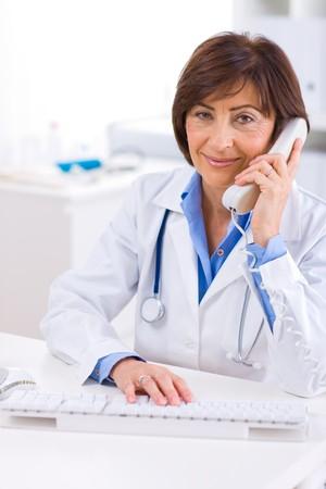 doctora: Superior femenino m�dico llamando por tel�fono, sonriendo.
