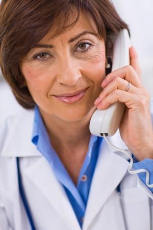 Senior female doctor calling on phone, smiling. Stock Photo - 4130707