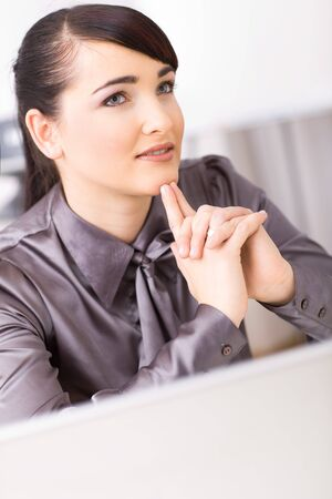 gratified: Young businesswoman thinking in her office, interlocking his hands.