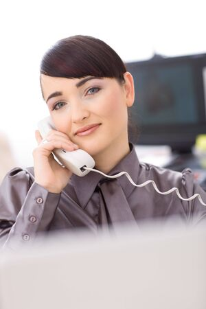 Young female customer service operator talking on landline phone, smiling. Stock Photo - 4130693